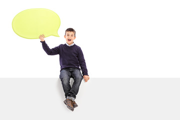 Male kid holding a speech bubble seated on panel