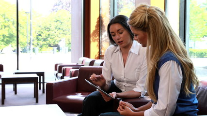 Smiling businesswomen having a meeting using tablet pc