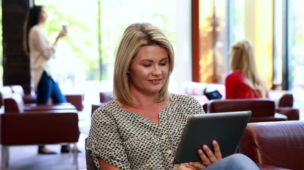 Focused woman using her tablet while smiling at camera