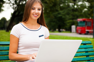 Woman using a laptop computer in a park