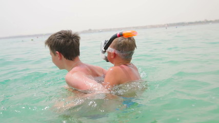 Two boys are playing and having fun in the sea