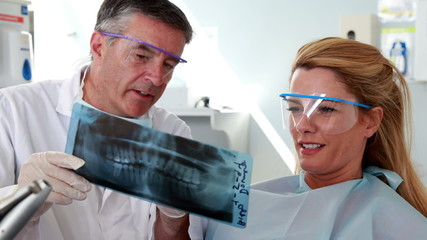 Dentist and patient in protective glasses looking x-ray together