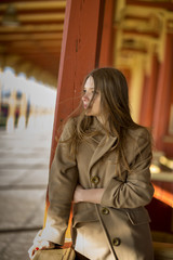 Woman in beige coat sees coming train