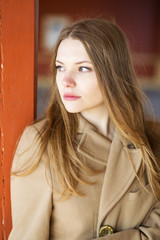 Woman in beige coat with sad face