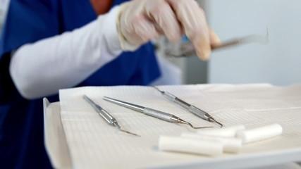 Smiling dentist preparing dental tools