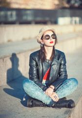 Young fashion beautiful girl in leather jacket, hat and sunglass