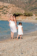 Happy family walking on the beach.