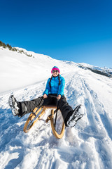Young woman having fun on a sledge