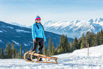 Smiling young woman with a sledge