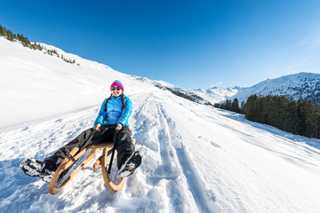 Young woman smiling on a sledge