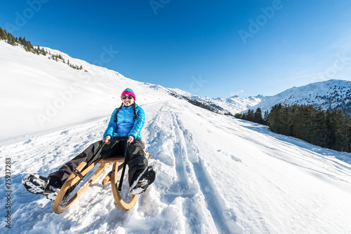 canvas print picture Young woman smiling on a sledge