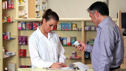Pharmacist advising customer on medicine
