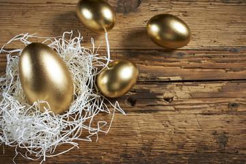 Golden eggs in nest on dark vintage wooden background