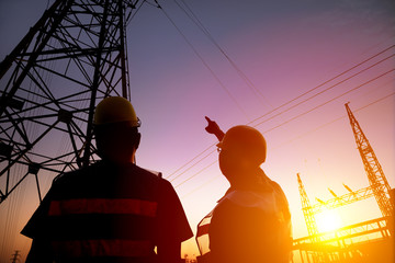 two worker watching the power tower and substation with sunset b