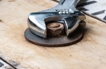 Pliers and nut on a wooden floor.