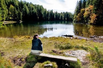 Frau sitzt auf einer Bank am See