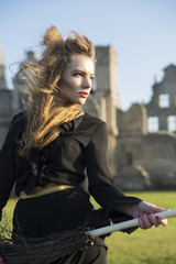 Woman at witch costume on ruins background
