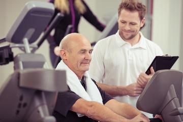 freundlicher trainer unterstützt senior im fitness-studio