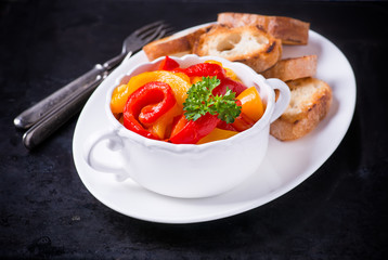 Roasted red and yellow peppers in white bowl