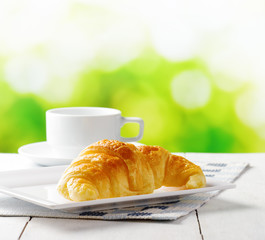 Cup of coffee and croissant on nature background