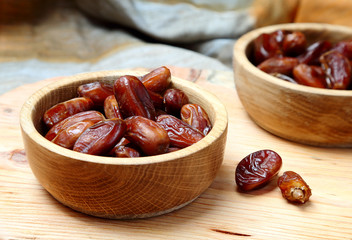 Fruits dates in wooden bowl  on  table