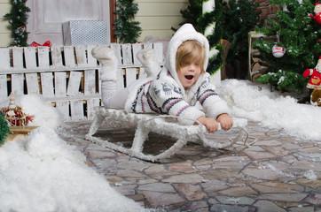 smiling child sledding in yard of snow winter