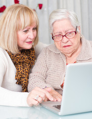 Daughter teaches her elderly mother using a computer