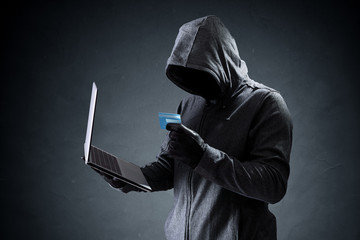 Computer hacker with credit card stealing data from a laptop
