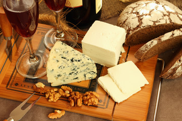 Cheese, glasses of wine and nuts on the board.