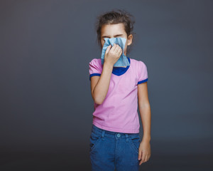 teen girl 5 years of European appearance sneezes sick, handkerch