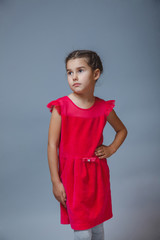 Teen girl in red dress looking thoughtfully into the distance
