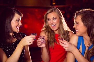 Pretty friends drinking shots together