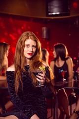 Pretty redhead drinking a cocktail