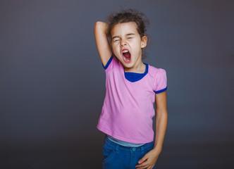 teen girl yawns sleepy opened her mouth on gray background