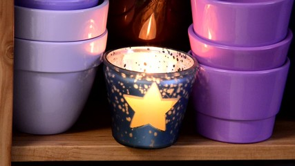 flowerpots with flaming candle in the shelf, rack focus