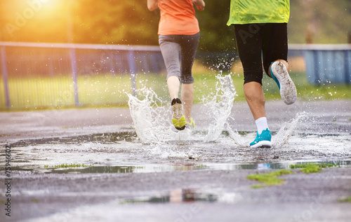 Couple running in rainy weather - 75946602