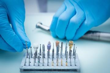 Gloved hands picking dental tools