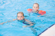 Two cute little girls in swimming pool