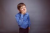 teenager boy yawns wants to sleep on gray background