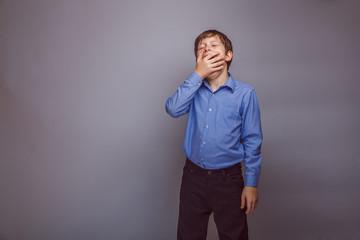 teenager boy yawns on gray background