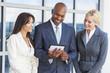 Interracial Men & Women Business Team With Tablet Computer