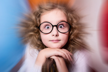 Portrait of surprised curly teen girl in glasses on the backgrou