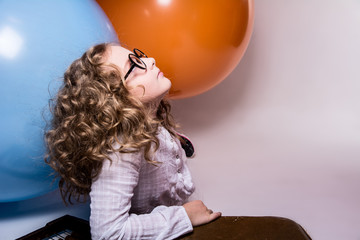 Portrait of curly teen girl in glasses on the background of larg