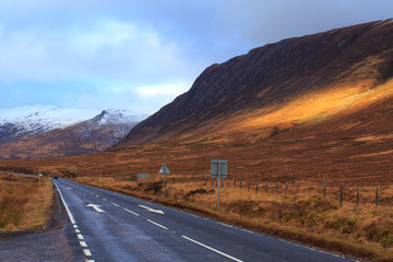 Empty road leading to snow-covered mountains