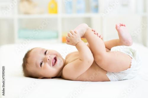 Leinwanddruck Bild baby lying on white bed and holding legs
