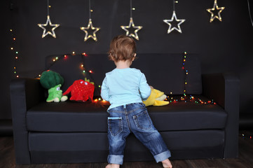 the kid plays on a sofa with toys