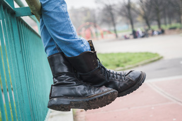 Detail of black boots in a city park