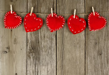 Group of Valentines Day hearts with clothespins hanging on wood