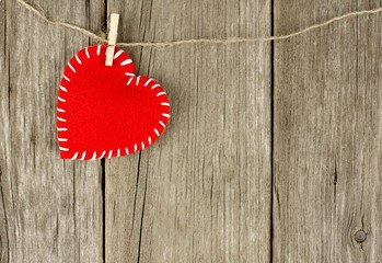 Valentines Day cloth heart hanging on old wood