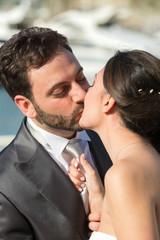 Bride pulls the tie of the groom while kissing him.